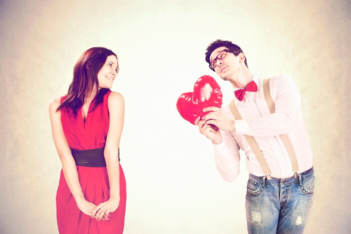 A man holding a heart balloon for a woman
